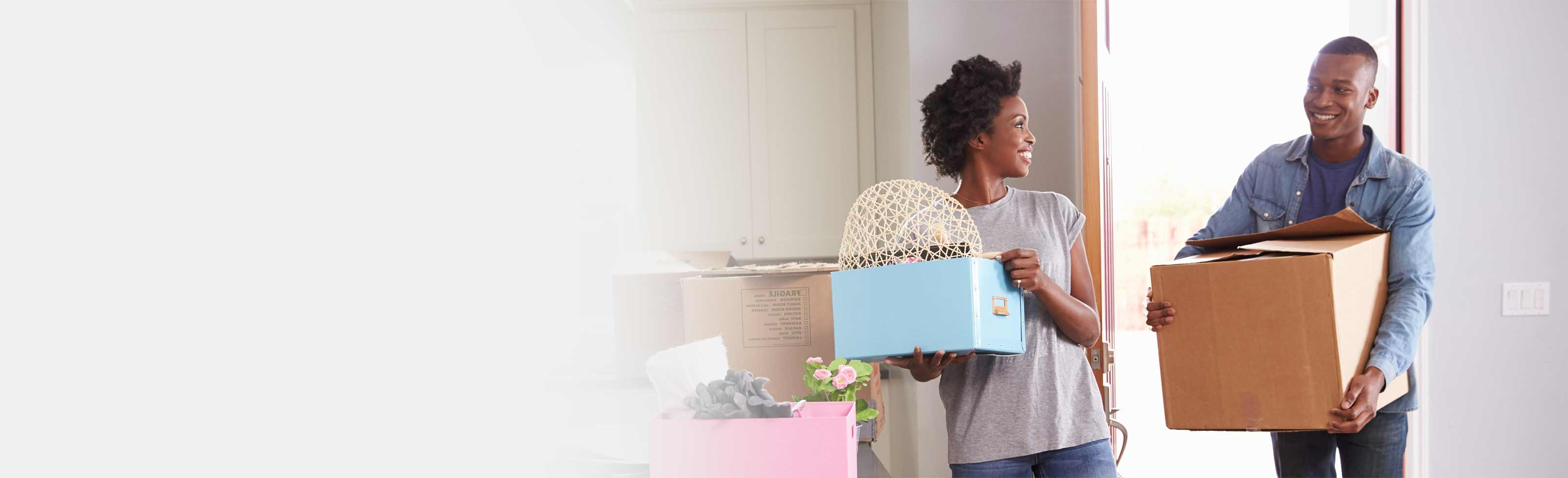 Young man and woman moving into home after using down payment assistance program.