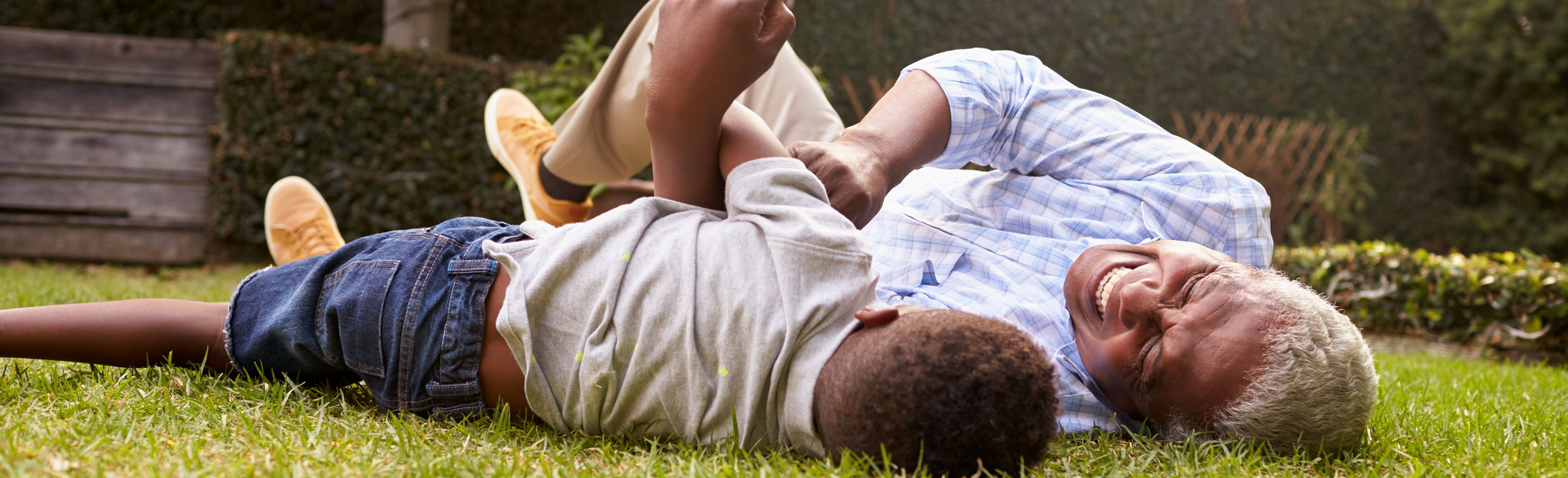 Man and grandson playing on lawn